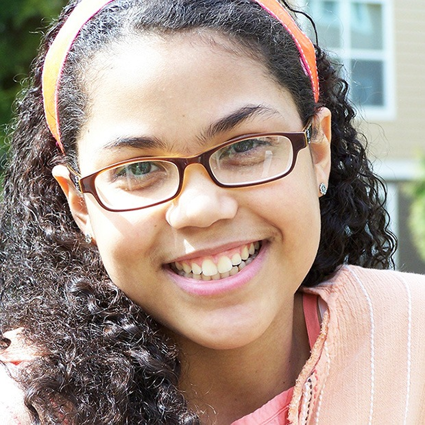 Young girl smiling with glasses and headband