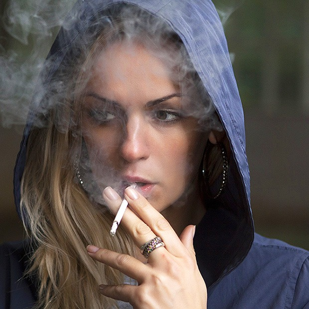Young adult woman in hood smoking a cigarette