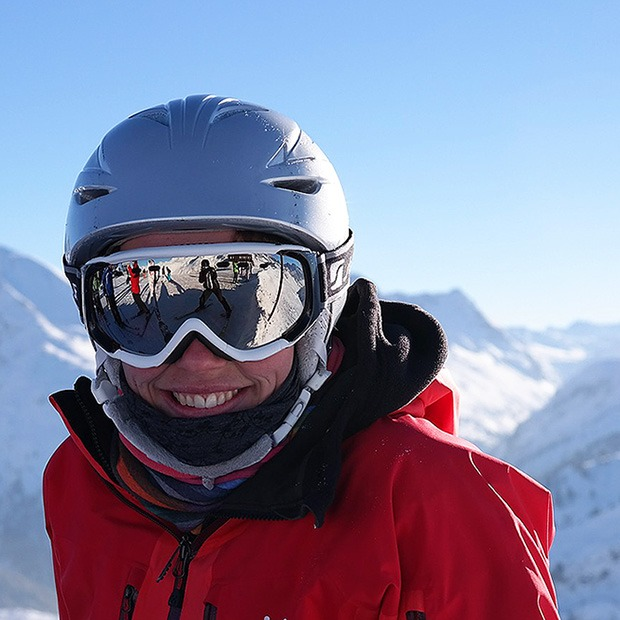 Adult smiling in snow gear, in the snow-capped mountains