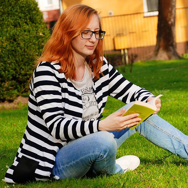 Adult woman reading a book outside with black glasses