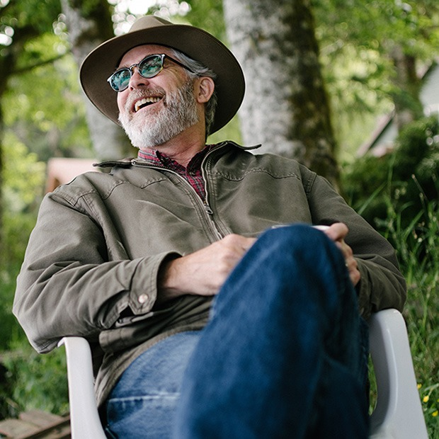 Older man sitting outdoors laughing with sunglasses