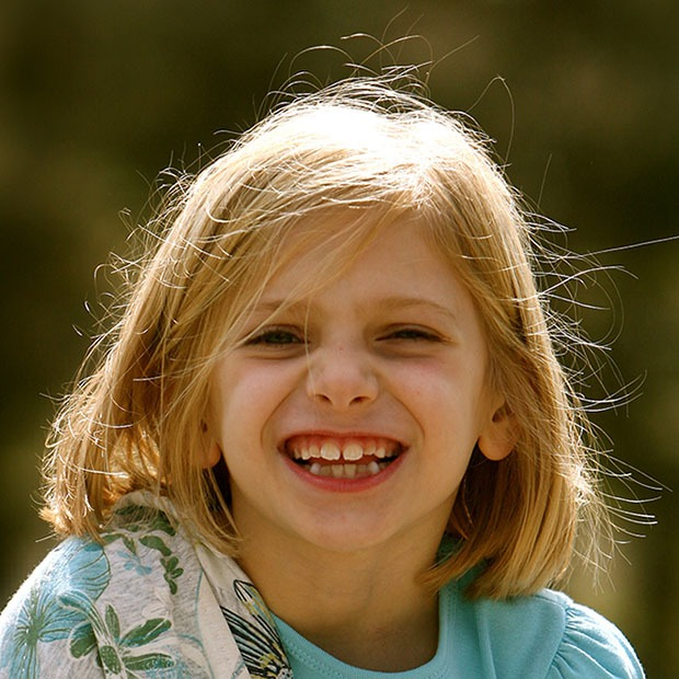 Young girl smiling happily at camera outside