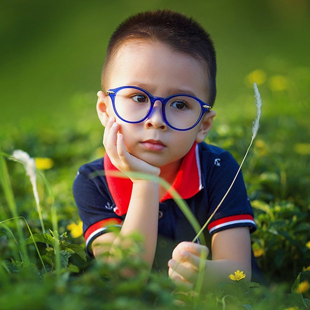 young boy with blue circular frames outside