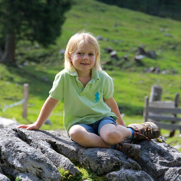 Young girl posing outside on a large rock