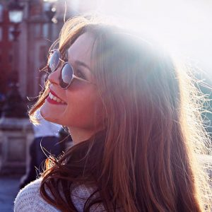Young girl with light against her hair, wearing sunglasses