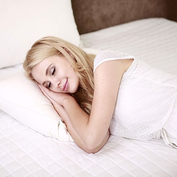 Young girl asleep on white bed and pillow