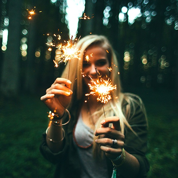 Young woman holding out lit sparklers