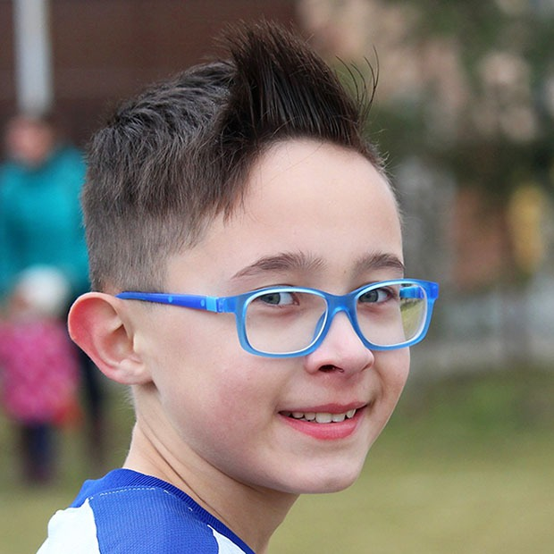 Young boy with blue glasses smiling