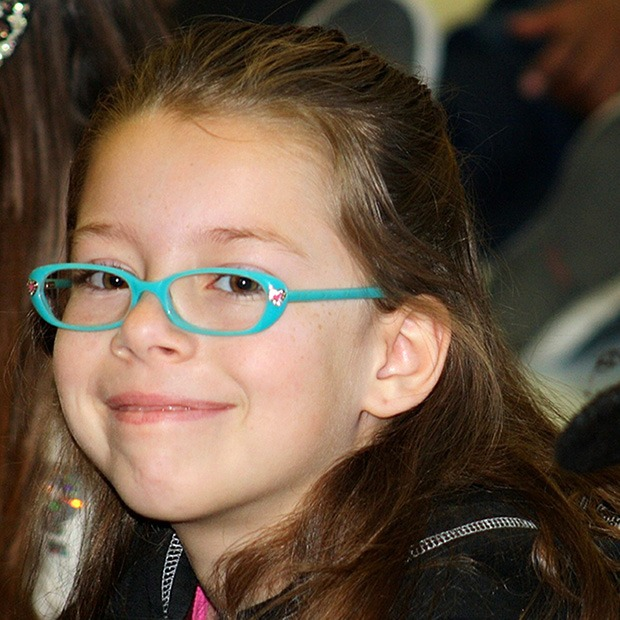 Young girl with blue green glasses, smiling