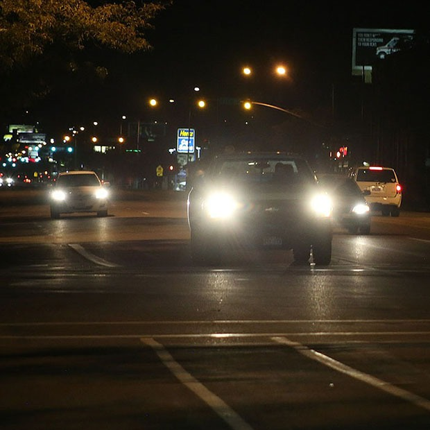 Picture of cars driving at night with headlights on