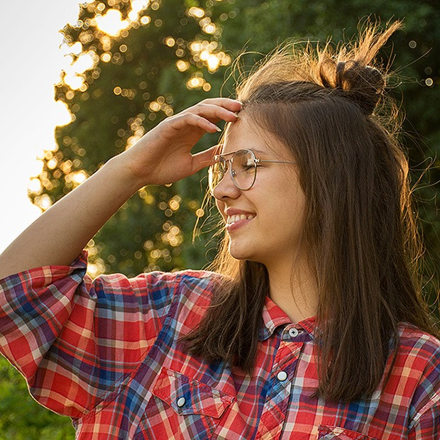 Young teenage girl smiling with glasses, getting face out of the way of her face