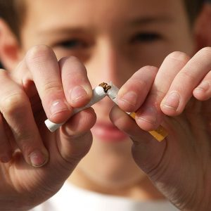 Closeup shot of young person destroying a cigarette close to screen