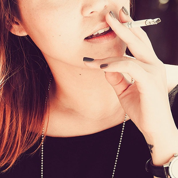 Closeup shot of young woman with a cigarette close to mouth