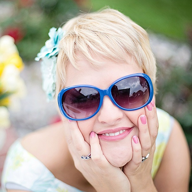Woman with sunglasses on, feeling face and smiling