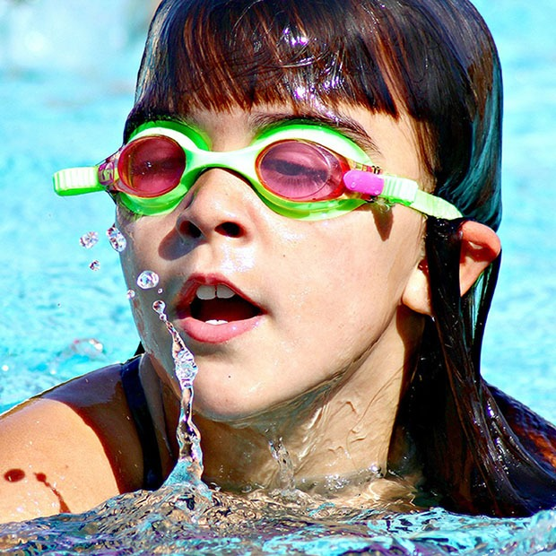 Young girl swimming with green goggles on