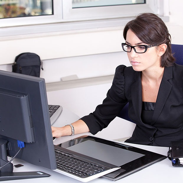 Young woman at work in office with black glasses