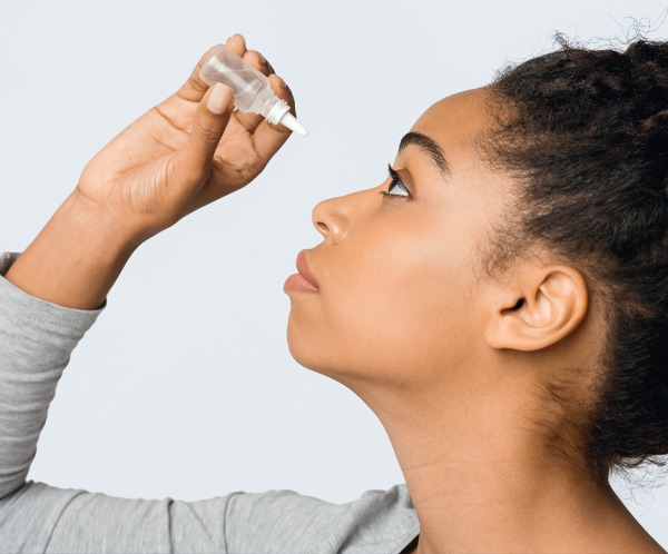 Young woman applying eyedropper, gray background